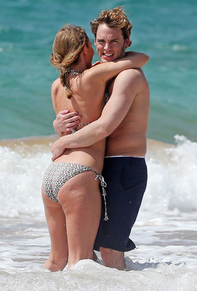 Hunger Games star Sam Claflin embraced his wife, Laura Haddock, during a day at the beach in Hawaii in April 2014.