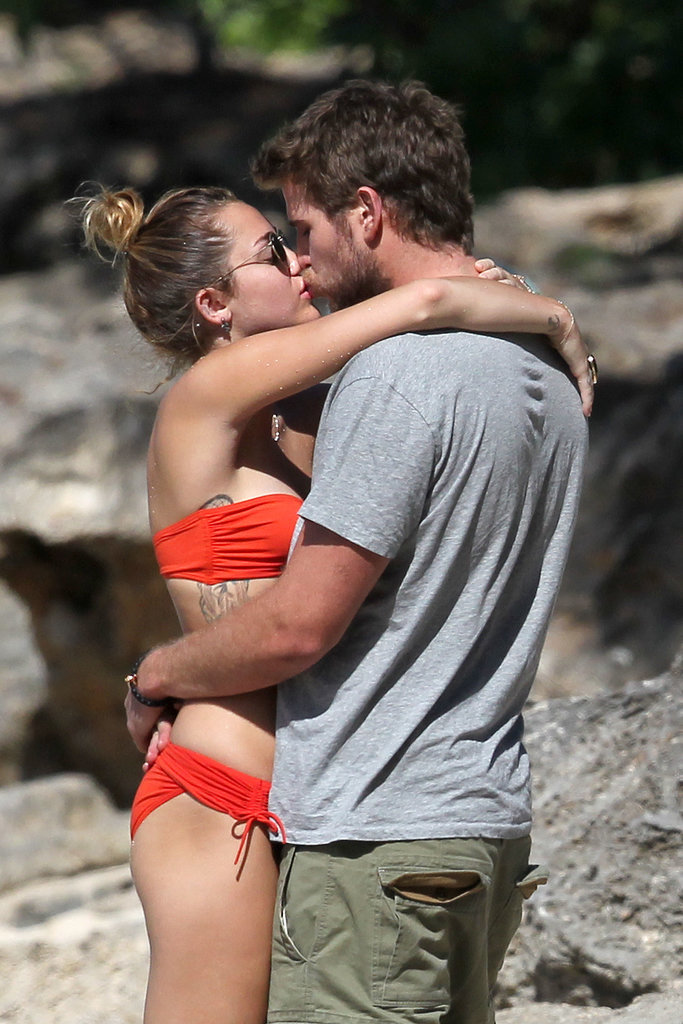 Then-couple Miley Cyrus and Liam Hemsworth shared sweet PDA on the beach in Hawaii in December 2011.