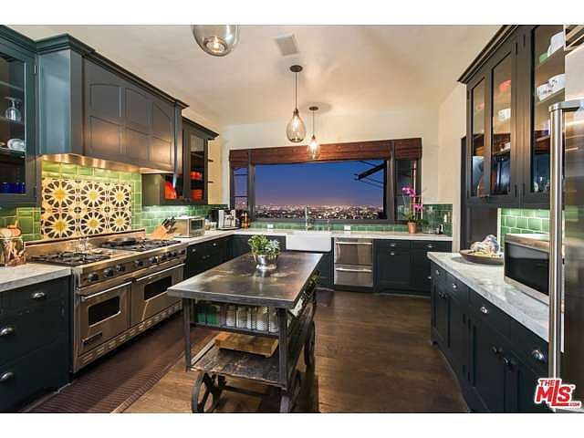A Spanish tile backsplash and green subway tiles add loads of personality.  Source: Coldwell Banker