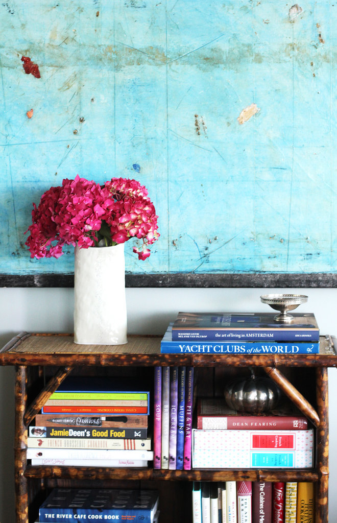 Contrasting colors make for a visually stunning effect. You just can't stop staring at those vibrant pink flowers against the blue painting!  Plus, the bamboo bookcase that she found at a flea market is such a distinct touch.