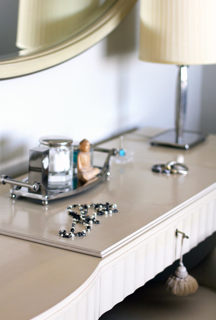 Even the vanity in the master bedroom features little details, like a hanging pom-pom and a classic mini silver tray.