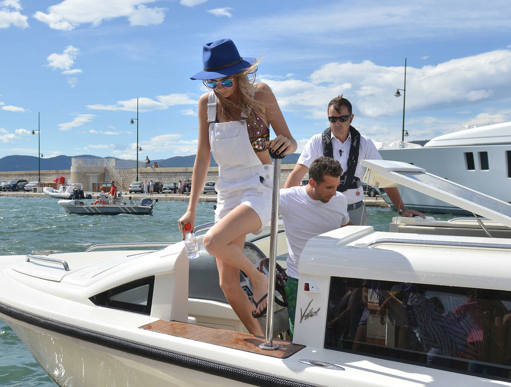 Cara stepped off the boat in a set of white Topshop overalls and a crop top.
