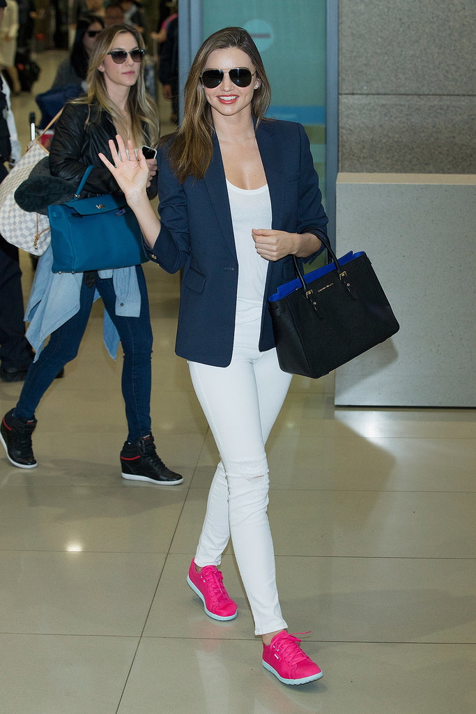 Leave it to Miranda to make a navy blazer and neon sneakers look fresh and effortless — especially when she just walked off a plane.