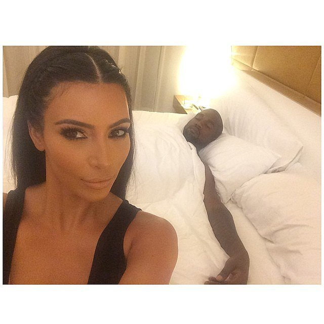 """After Kanye took center stage and performed, the newlyweds headed back to their bedroom, where Kim took an hilarious selfie showing Kanye sleeping in the background. """"Side chicks be like....,"""" Kim captioned it.  Source: Instagram user kimkardashian"""