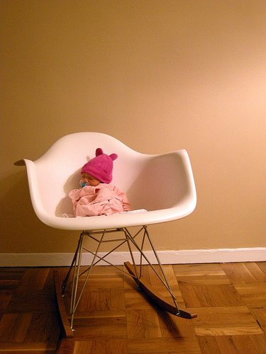 Here's an Eames rocker fulfilling its original purpose — rocking a newborn. Source