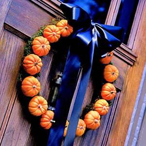 Make a mini-pumpkin wreath with pumpkins, moss, and a dark black bow.