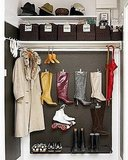A gray with undertones of brown is both cool and warm. But you should also keep it from feeling too dark by painting your moldings in a bright white. It's great for a Fall and Winter space, like this boot, hat, and coat closet. Source