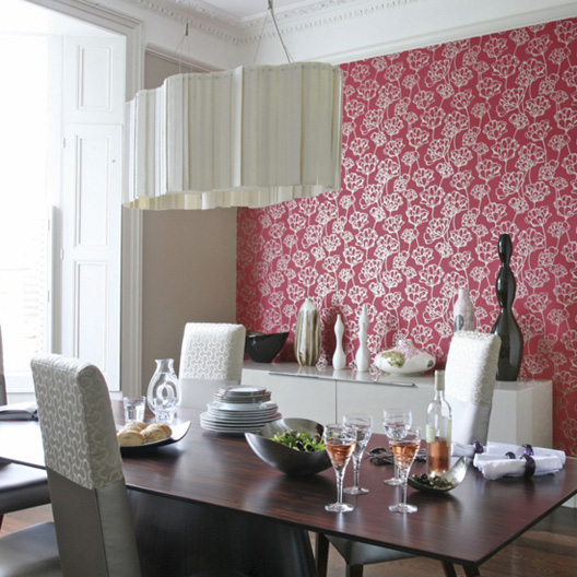 The floral print on this red wallpaper lends a playful feel to this modern dining room.  Source