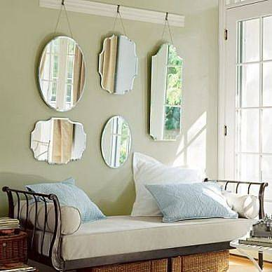 Five unframed mirrors in decorative shapes create a focal point behind this daybed. Source