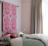Avoid long-term pink commitment by hanging a bright textile as an alternative to a headboard. It can easily be switched out for another fabric. Source