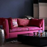 A pink sofa can look incredibly moody and thoughtful next to a dark, brooding black wall.  Source