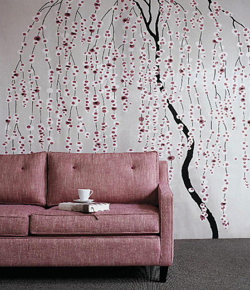 A tweedy texture adds a masculine quality to this pink sofa, while the elaborate wall mural behind creates a whimsical feel.