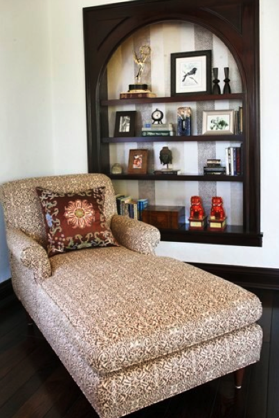 Jason Martin chose a brown pattern for a key element of furniture in one of the rooms he decorated. The busy patterns of the pillow and lounge chair are offset by the solid brown in the built-in cabinet behind it. Source