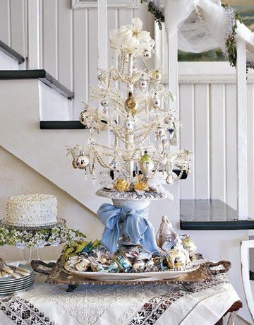 A tabletop tree in an all-white palette is elegant on a serving table. Source