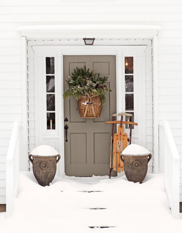 If you live in a snowy climate, use seasonal props, like an antique sled, to add personality to your front door. Source