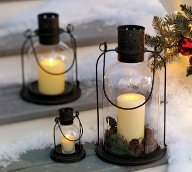 Dress up simple outdoor hurricane lanterns by placing pinecones and greenery inside them.