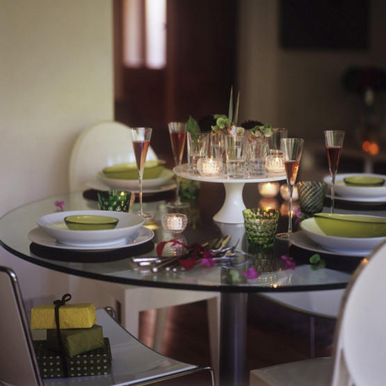 Use cake plates to elevate votives. Mismatched tableware adds an eclectic, bohemian feel to this holiday table.  Source