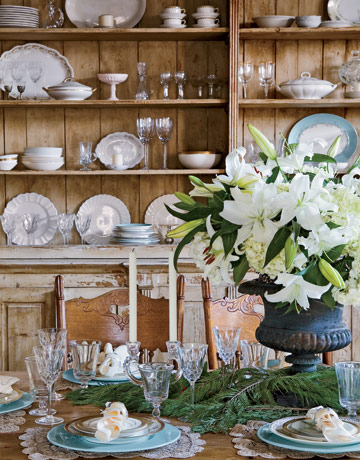 Use a large urn for a dramatic display of lilies. Garlands of pine boughs emphasize the holiday.  Source