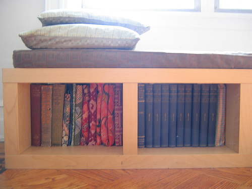 This Ikea Lack shelf, topped by a handmade cushion, proves that bookshelves can do double duty as comfy reading furniture.  Source:  Flickr User shnnn