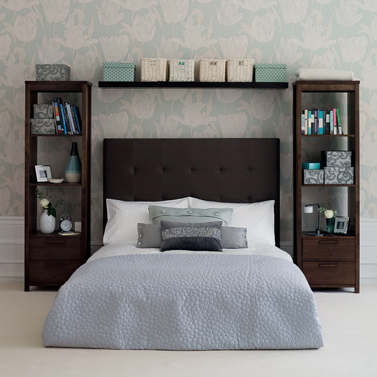 Open storage works here due to a restrained color palette and handsome storage containers. The bedside shelves also act as tables that can be used for bedside necessities such as an alarm clock and reading material. Source
