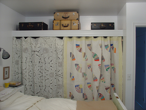 In this bedroom, a closet was improvised by installing a tall shelf and then hanging a fabric divider to hide hangers and clothing. I also love the use of vintage suitcases for additional storage on top. Source:  Flickr User Barb McMahon