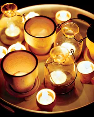 Cluster candles on a tray, using a variety of vessels, including terra cotta pots. Source