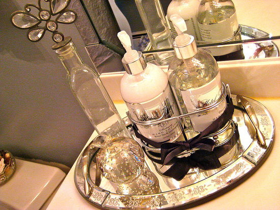 Set a mirrored tray or even a small mirror on your countertop to house crystal perfume bottles and elegant jars of soap and lotion.