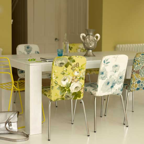 These boldly upholstered floral chairs, paired with yellow metal chairs, add a punchy Palm Beach flair to this room.  Source