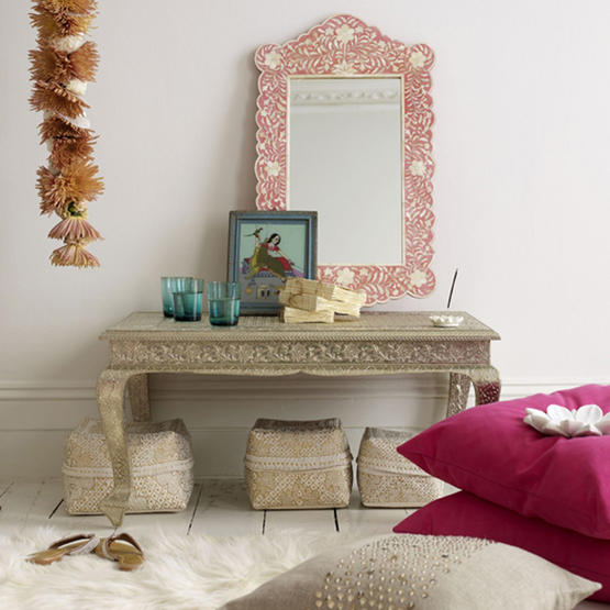 This room's Indian vibe is conveyed throughout the space. The white, wide floorboards, and more subtle footstools contrast with the bright pink pillows and orange inlaid mirror. Source