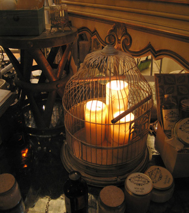 A birdcage with different sizes of pillar candles creates ethereal mood lighting. Source