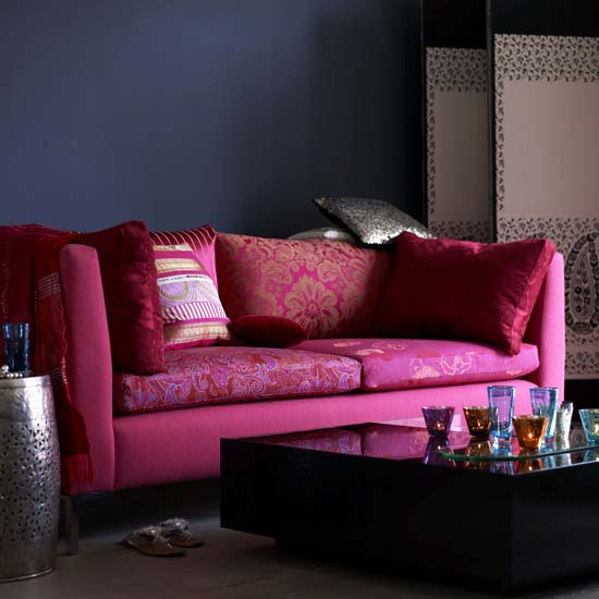 Pink and orange mix it up in the patterns of these throw pillows, and help to cut the over-the-top pink effect of the sofa.  Source