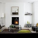This fireplace is minimalist and modern, yet still cozy, thanks to the textiles used in the room. Source