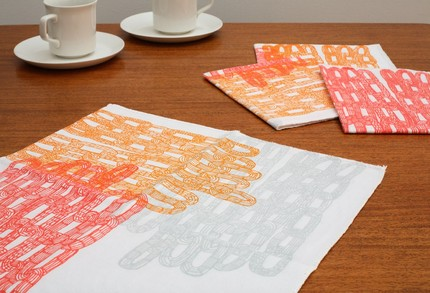 The Chain Pattern Napkin ($6 each) features screenprinted cascading chains in gray, scarlet, and orange with serged edges. Not only is it colorful, but the illustration is stunning!
