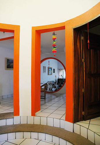 An unusual home's multiple doorways are accented with orange paint.  Source:  Flickr User Wonderlane