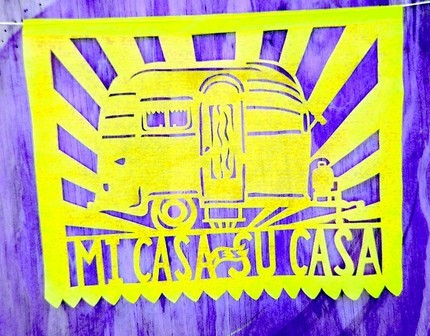 """Mi Casa Es Su Casa"" translates to ""My House Is Your House""and is, as you can see, inspired by vintage Airstream trailers or ""silver bullets."" One Mi Casa Es Su Casa Banner ($23) is 13 feet long with 9 flags upon the banner."