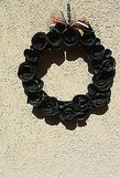 This Recycled Paper Black Rose Wreath ($25) is very chic, although I'd remove the ribbons from the top.