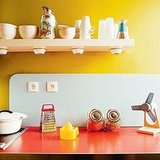 Sunny yellow is just plain cheerful. But it's also a great way to distract from dated countertops or floors. Source