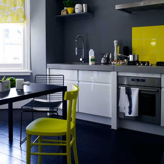 Bright neon pops of color add a hip modern touch to this kitchen's dark interiors and floors. Source