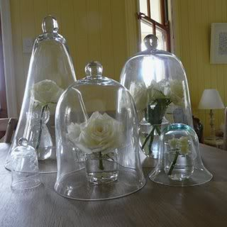 Use varying sizes of cloches to display individual cut flowers. Together, they make a stunning arrangement.  Source