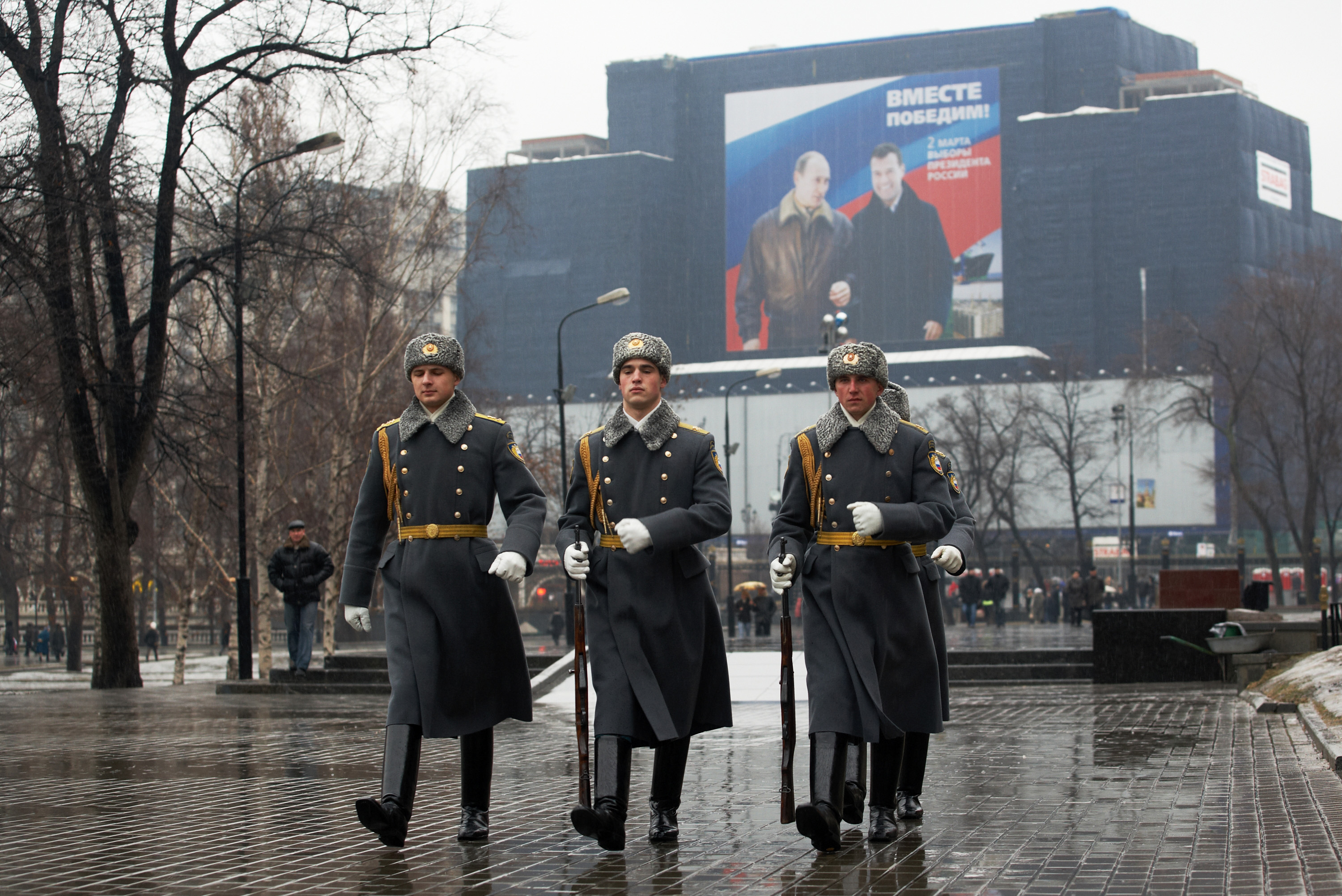 Guards of honor walk past a large election poster.