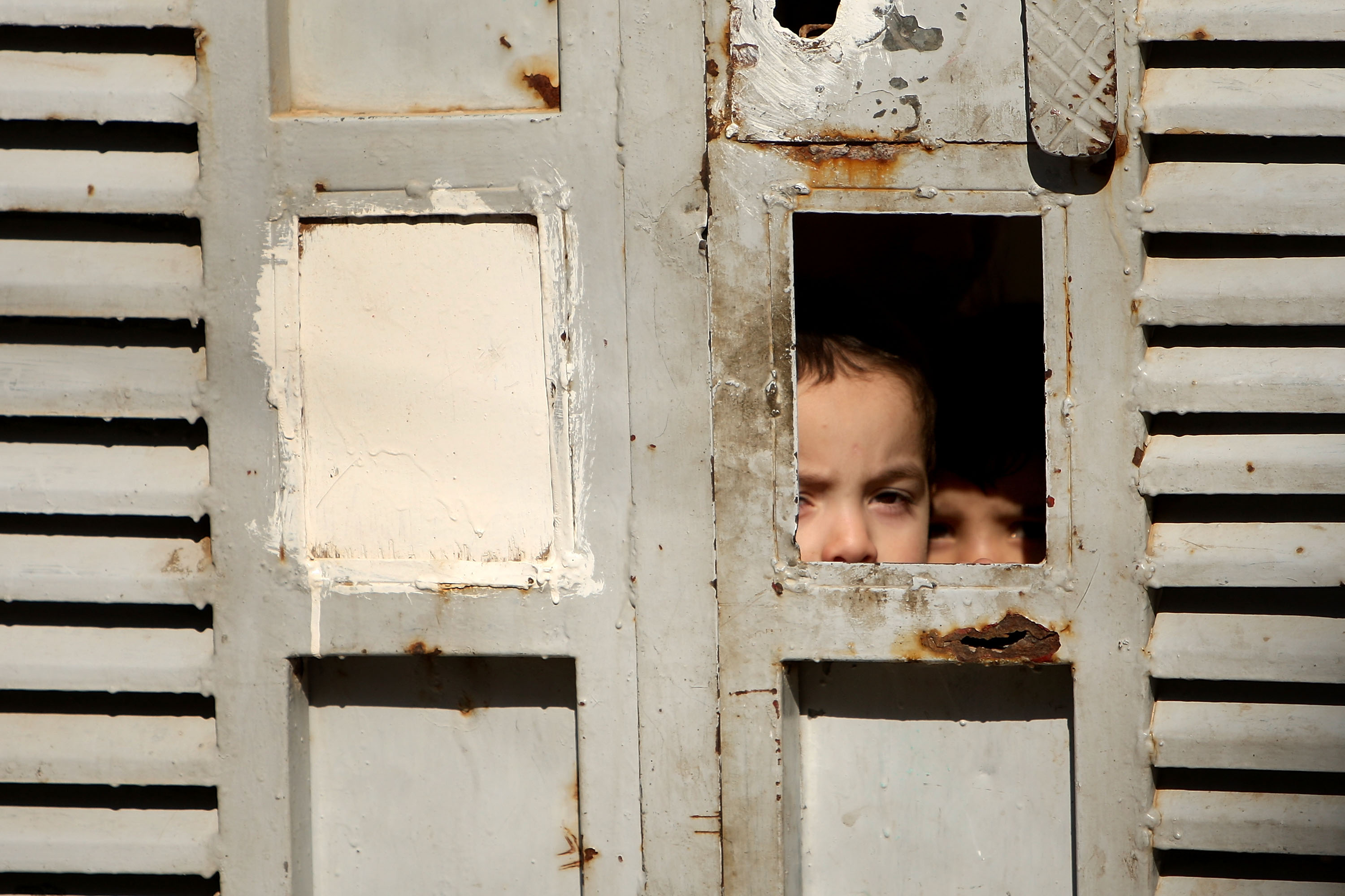 Children look out from a gate in Baghdad's Doura neighborhood March 7, 2008.