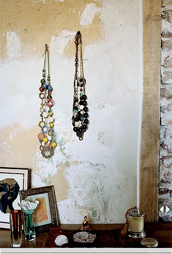 Here, beaded necklaces hung at varying heights add a shot of glamour to an unfinished wall. Source