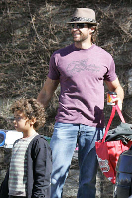 Hugh Flexes His Biceps While Carrying Kiddie Bags