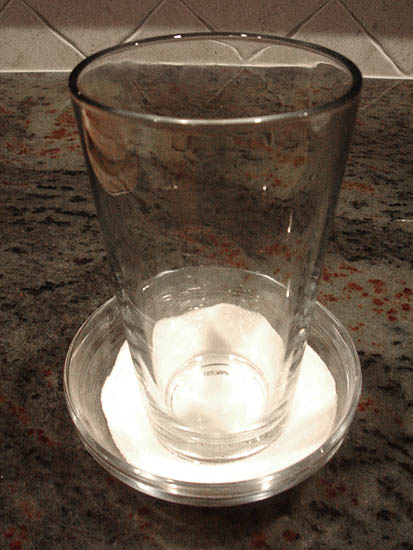 Dipping the bottom of a glass in sugar to prevent sticking to the cookie dough balls.