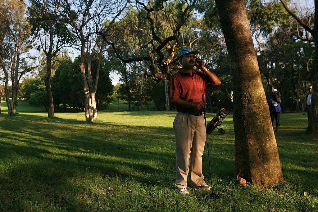 Leisure time! A man talks on his phone at a golf course.