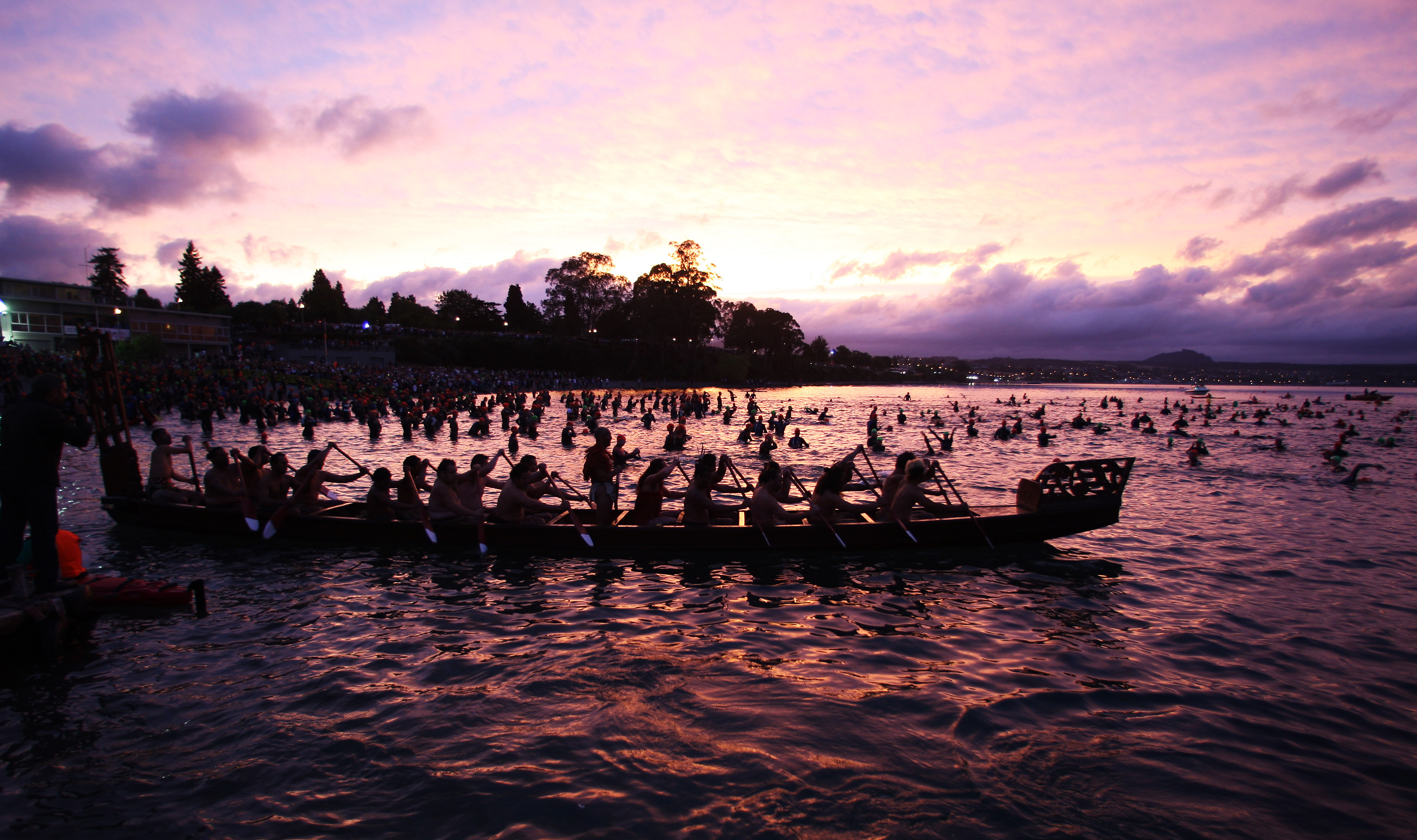 A maori Waka (war canoe) escorts competitors during March's NZ Ironman.