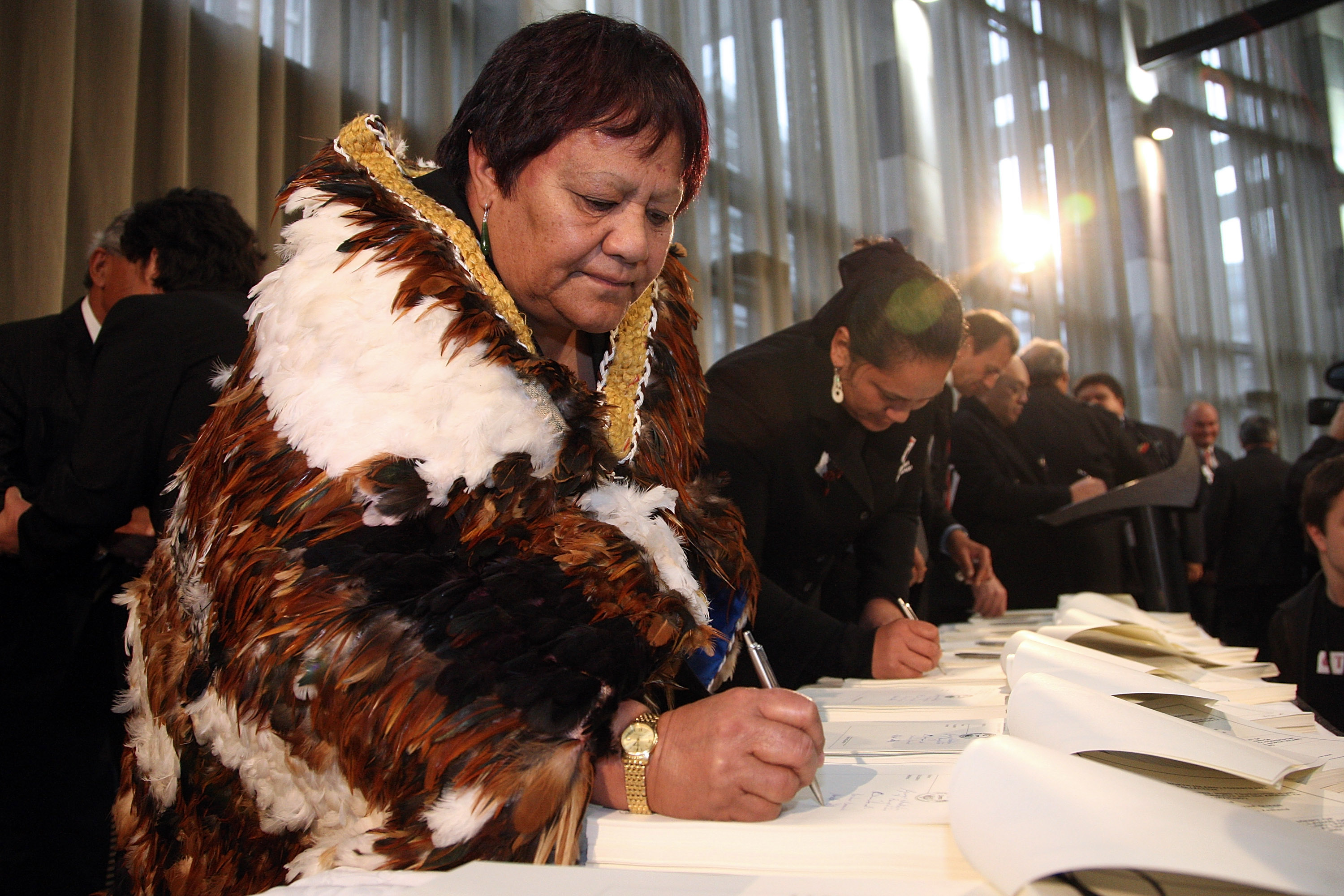 Iwi representatives sign documents.