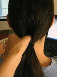 Use your fingers to separate hair above ponytail holder, creating a hole.