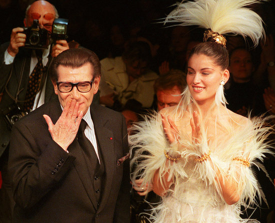 2000: Yves Saint Laurent blows a kiss at the end of his Spring 2000 couture presentation, with bride Laetitia Casta standing by.