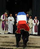 Pallbearers carry Saint Laurent's coffin.
